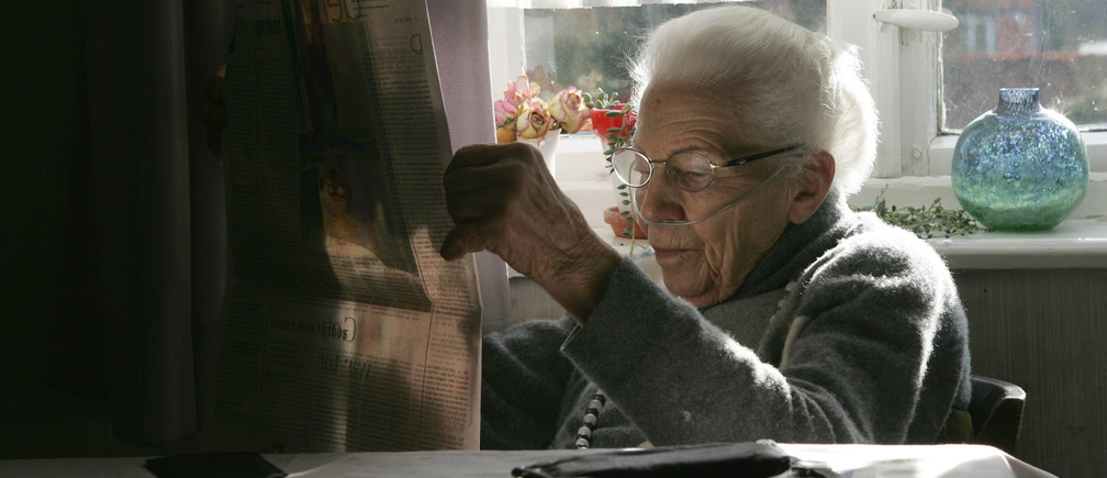 Ilse Westphal, 92-year-old, reads the newspapers as she receives her daily oxygen therapy for a chronic pulmonary disease, in the living room of her farmhouse in the small village of Gross Lafferde near Hanover, northern Germany, April 15, 2006.    REUTERS/Christian Charisius - RTR1CKX6