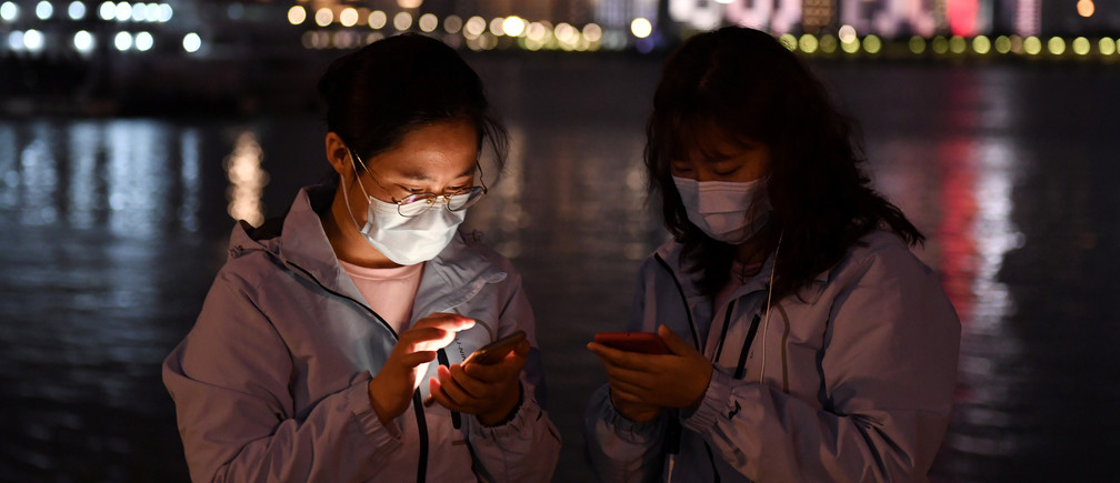 Medical workers from outside Wuhan check their mobile phones at a riverside park by the Yangtze River in Wuhan of Hubei province, the epicentre of China's coronavirus disease (COVID-19) outbreak, March 26, 2020. REUTERS/Stringer  CHINA OUT. - Coronavirus china virus health healthcare who world health organization disease deaths pandemic epidemic worries concerns Health virus contagious contagion viruses diseases disease lab laboratory doctor health dr nurse medical medicine drugs vaccines vaccinations inoculations technology testing test medicinal biotechnology biotech biology chemistry physics microscope research influenza flu cold common cold bug risk symptomes respiratory china iran italy europe asia america south america north washing hands wash hands coughs sneezes spread spreading precaution precautions health warning covid 19 cov SARS 2019ncov wuhan sarscow wuhanpneumonia  pneumonia outbreak patients unhealthy fatality mortality elderly old elder age serious death deathly deadly