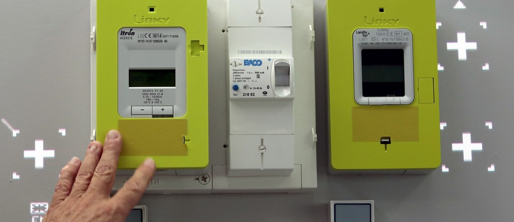 A man shows Linky electricity meters displayed for demonstration in the showroom of Nice Grid, a smart solar district demonstration project, in Carros, southeastern France, June 11, 2015.