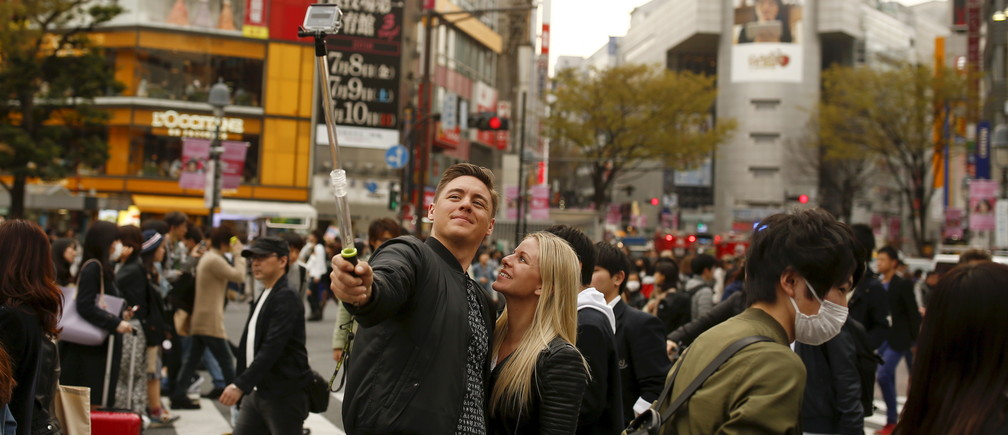People take a selfie at Shibuya junction, which is popular among tourists, in Tokyo, Japan, March 30, 2016.  Japanese Prime Minister Shinzo Abe set on Wednesday an ambitious target to double the number of foreign visitors and the amount of money they spend in the country by 2020 to breathe life into a flagging economy.  REUTERS/Thomas Peter - GF10000365406