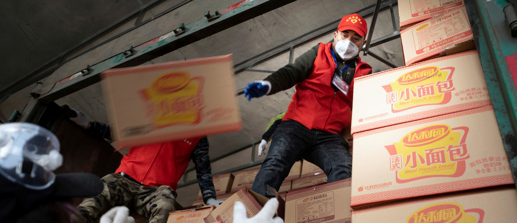 Volunteers wearing face masks unload food supplies delivered from Xiaogan, Hubei province, on a truck following the outbreak of the coronavirus disease (COVID-19), in Suifenhe, a city bordering Russia in China's Heilongjiang province, April 19, 2020. Picture taken April 19, 2020. China Daily via REUTERS  ATTENTION EDITORS - THIS IMAGE WAS PROVIDED BY A THIRD PARTY. CHINA OUT. - RC268G9FVOG7