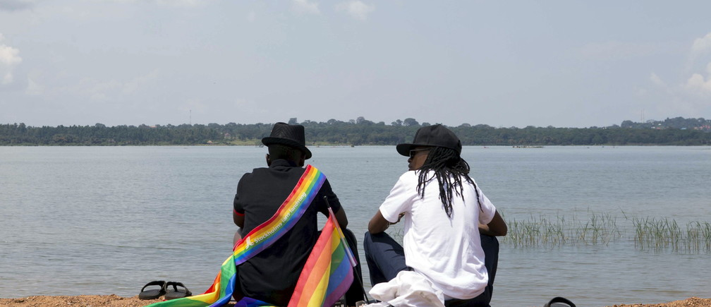A gay couple chats by a beach before a parade by members of the lesbian, gay, bisexual and transgender (LGBT) community in Entebbe, southwest of Uganda's capital Kampala, August 8, 2015