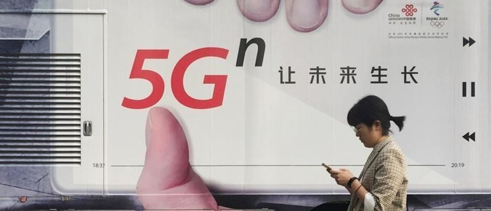 A woman using her mobile phone walks past a vehicle covered in a China Unicom 5G advertisement in Beijing, China September 17, 2019. Picture taken September 17, 2019. REUTERS/Stringer  ATTENTION EDITORS - THIS IMAGE WAS PROVIDED BY A THIRD PARTY. CHINA OUT. - RC1D8F007DB0