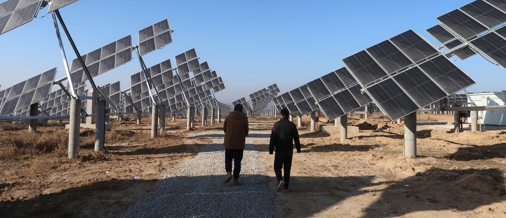 Workers walk at a solar power station in Tongchuan, Shaanxi province, China December 11, 2019. Picture taken December 11, 2019.