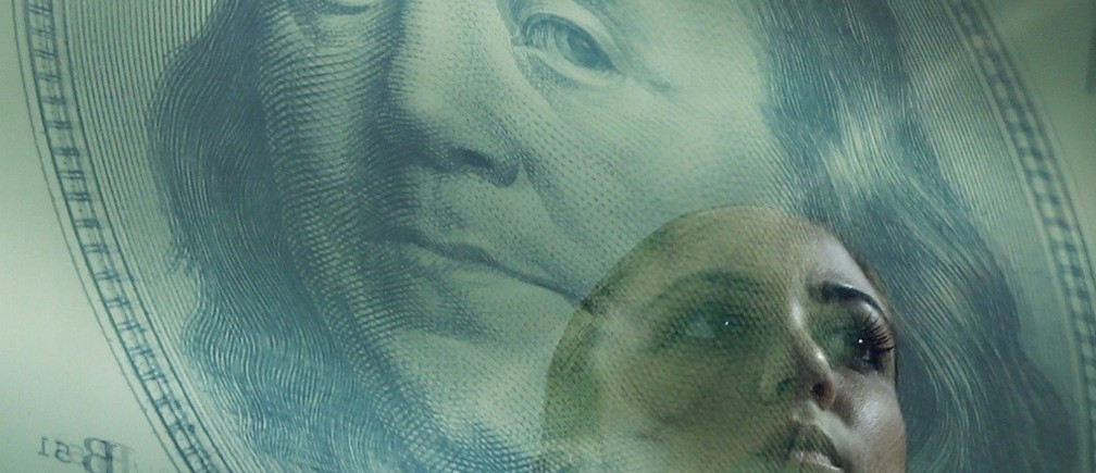 A woman passes by a reflection of a poster of a Benjamin Franklin 100 dollar bill at a money changer in Singapore November 3, 2014. A year-long investigation into allegations of collusion and manipulation by global currency traders is set to come to a head on Wednesday, with Britain's financial regulator and six big banks expected to agree a settlement involving around ?1.5 billion ($2.38 billion) in fines. The settlement comes amid a revival of long-dormant volatility on the foreign exchanges, where a steady rise of U.S. dollar this year has depressed oil prices and the currencies of many commodity exporters such as Russia's rouble, Brazil's real and Nigeria's naira - setting the scene for more turbulence on world financial markets in 2015. Picture taken November 3, 2014. REUTERS/Edgar Su (SINGAPORE - Tags: CRIME LAW BUSINESS POLITICS)ATTENTION EDITORS: PICTURE 12 OF 23 FOR WIDER IMAGE PACKAGE 'ANOTHER DAY ANOTHER DOLLAR'TO FIND ALL IMAGES SEARCH 'CURRENCY TRADERS' - RTR4DT04