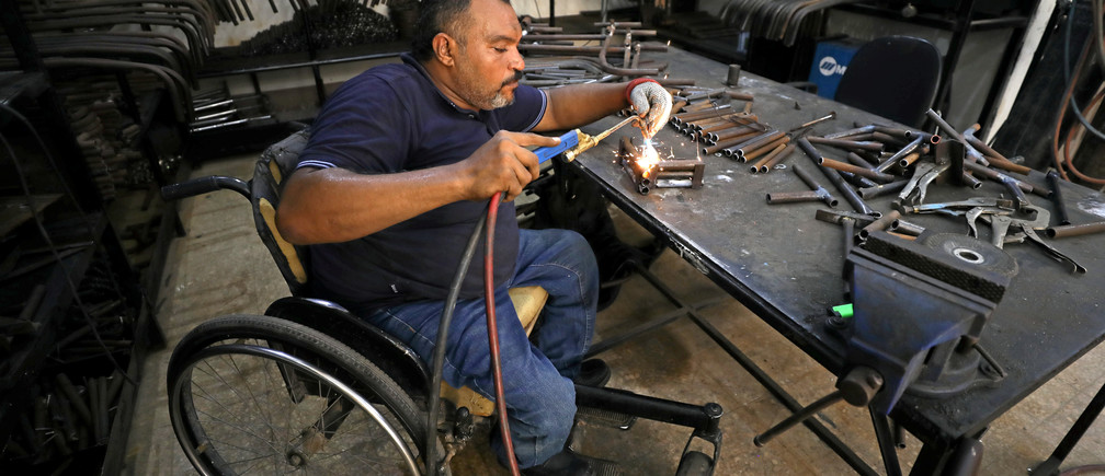 A disabled Egyptian man works in a workshop that manufactures products for the poor disabled in Cairo, Egypt August 8, 2017. Picture taken August 8, 2017. REUTERS/Mohamed Abd El Ghany - RC141769AFE0