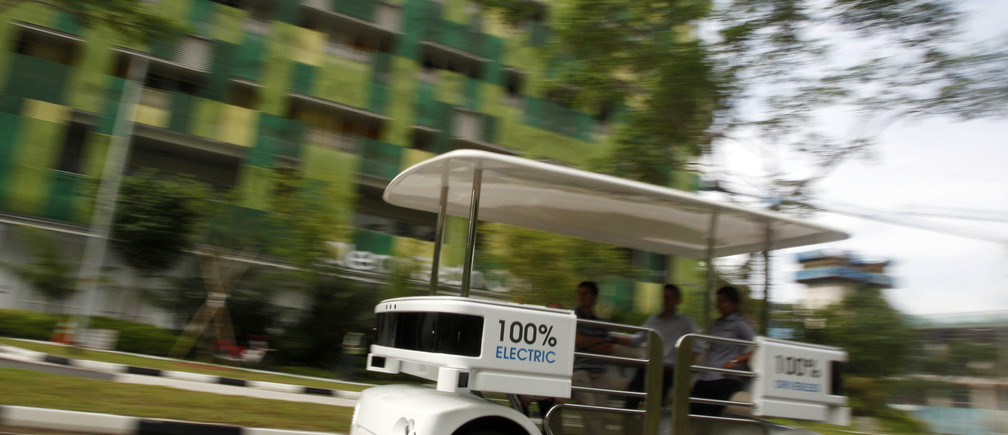 People ride on a driverless electric vehicle at the Nanyang Technological University (NTU) in Singapore September 4, 2013. The eight-passenger shuttle vehicle named Navia makes use of laser rangefinders, cameras and a navigation software that allows it to move autonomously and safely at speeds up to 20 km/h, according to manufacturer Induct. Induct and NTU's Energy Research Institute has teamed up to test and optimize Navia in a two-year collaboration aimed at improving the reliability of the battery and reducing charging time, according to local media. REUTERS/Edgar Su (SINGAPORE - Tags: TRANSPORT SCIENCE TECHNOLOGY SOCIETY ENERGY EDUCATION) - GM1E9941K2Y01
