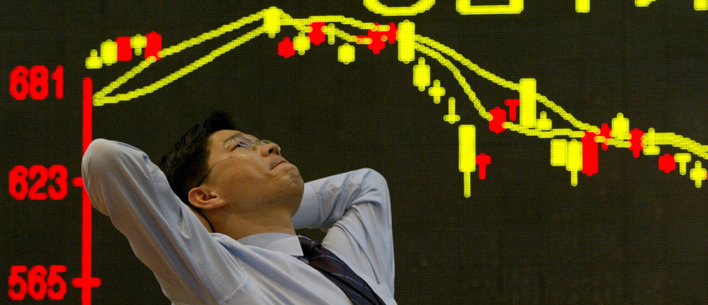 A South Korean employee of a security firm reacts in front of a graph showing stock price in Seoul, 2003
