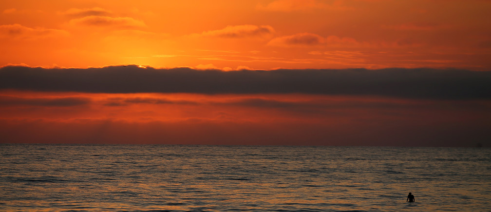 A lone surfer watches the sun set behind a cloud off the beach in Encinitas, California, U.S., July 5, 2017. REUTERS/Mike Blake - RTX3A831