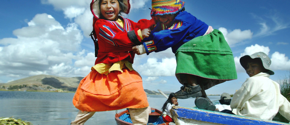 PICTURES OF THE YEAR 2004  Uro children play on a boat on Uro island in Lake Titicaca, November 5, 2004. The Floating Islands of Uros are made by natives from compacted beds of totora reeds. The islands are located in Lake Titicaca, the worlds highest navigable lake at over 4,000 meters above sea level. The Uros people fish and hunt, but tourism is the main source of livelihood. PHOTO TAKEN NOVEMBER 5. REUTERS/Pilar Olivares - RTRIEKO