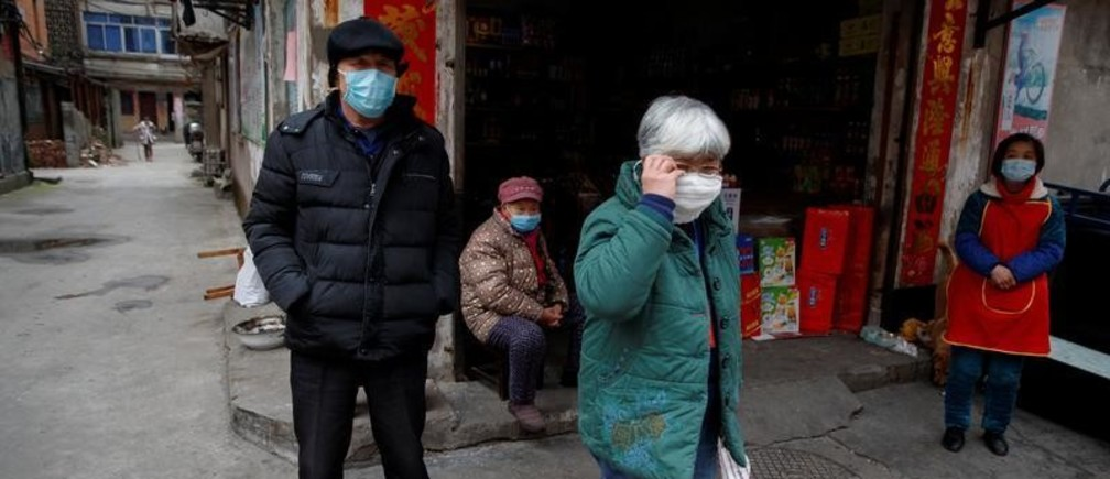 People wear protective masks in an old neighbourhood of Jiujiang, Jiangxi province, China, as the country is hit by an outbreak of novel coronavirus.  February 2, 2020.  REUTERS/Thomas Peter - RC2GSE9E07YS