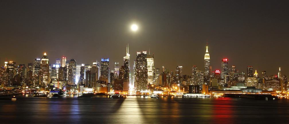 A full moon rises over the New York skyline above 42nd Street (C), seen from across the Hudson River in Weehawken in this New Jersey April 25, 2013 file photo. New York City is iconic in any weather, but the warm season adds a special flavour to its bustling streets, leafy parks and world-famous skyline. The summer is about to draw to a close, as fall begins in the northern hemisphere with the Autumnal Equinox on September 22. Picture taken April 25, 2013. REUTERS/Gary Hershorn/Files (UNITED STATES - Tags: CITYSCAPE SOCIETY) ATTENTION EDITORS: PICTURE 04 OF 40 FOR PACKAGE  'NYC - A SEASON IN THE CITY' SEARCH 'NYC HERSHORN' FOR ALL IMAGES - RTX13TBE