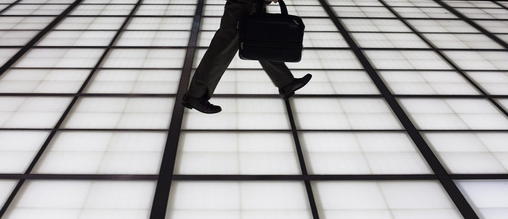 People cross an illuminated floor at a banking district in central Tokyo November 27, 2014. Japan's jobless rate fell and the availability of jobs edged higher in October from the previous month, government data released on Friday showed.