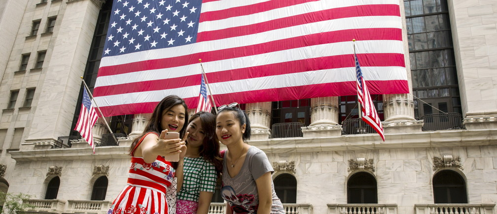 Chinese tourists take photographs of themselves outside of the New York Stock Exchange shortly after the opening bell in New York, July 8, 2015.  REUTERS/Lucas Jackson  - GF10000152773
