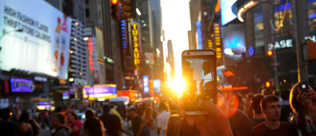 """A man takes a photo with her phone as the sun sets over Manhattan aligned exactly with the streets in a phenomenon known as """"Manhattanhenge"""", in New York City, U.S., July 11, 2016.  REUTERS/Mark Kauzlarich - RTSHGZ3"""