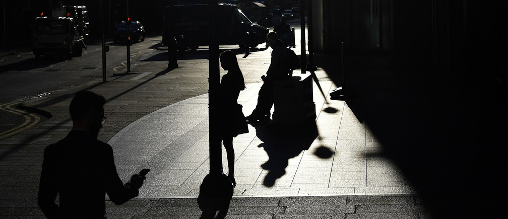 The early morning sun silhouettes commuters as they make their way through Canary Wharf in London, Britain September 5, 2019.  REUTERS/Dylan Martinez     TPX IMAGES OF THE DAY - RC164599A350