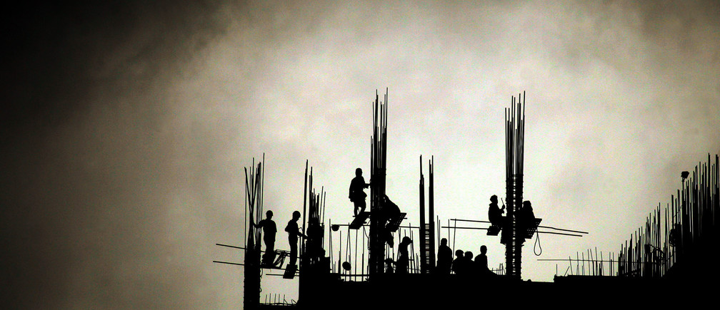 Indian workers engage in the construction of a high-rise building on a cloudy day in Bombay June 29, 2005. India's southwest monsoon has spread to about three-quarters of the country, including the capital New Delhi, which has led to increased sowing of winter crops, weather officials and traders said on Monday. REUTERS/Arko Datta  AD/KS - RP6DRMTULNAA