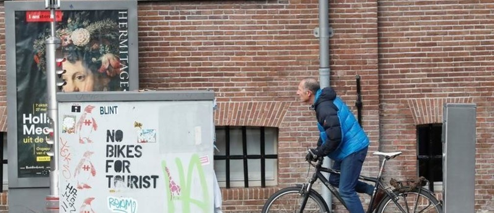 """A cyclist rides past a graffiti reading """"no bikes for tourist"""" in central Amsterdam, Netherlands, December 1, 2017.  REUTERS/Yves Herman - RC13F58BC9E0"""