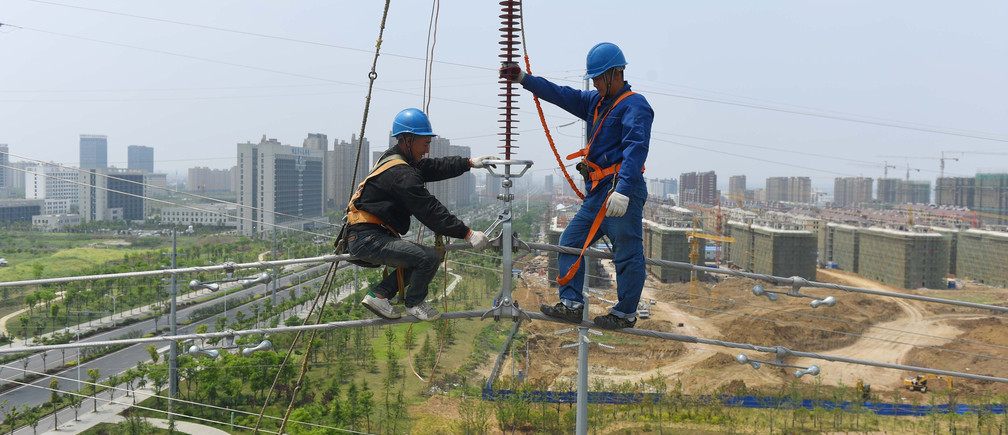 Labourers work on an electricity transmission tower in Chuzhou, Anhui province, China, May 16, 2017. REUTERS/Stringer    ATTENTION EDITORS - THIS IMAGE WAS PROVIDED BY A THIRD PARTY. EDITORIAL USE ONLY. CHINA OUT. NO COMMERCIAL OR EDITORIAL SALES IN CHINA. - RTX360S2