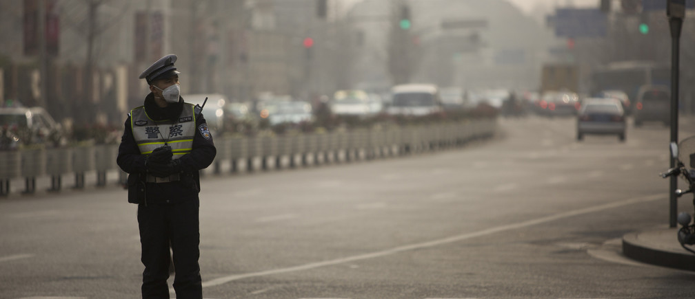 A policeman wearing a face mask stands on a road during a hazy day in Shanghai, January 20, 2014. Chinese steelmakers and power plants are being forced to shop around for higher-quality raw materials to meet tougher air pollution standards, a move that will be a boon for global mining giants that produce premium-grade iron ore and coal. Picture taken January 20, 2014.