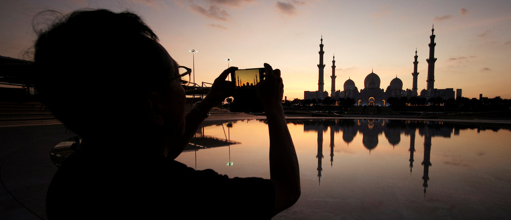 A visitor takes photos of Sheikh Zayed Mosque with their smart phone in Abu Dhabi, United Arab Emirates, December 25, 2018. Picture taken December 25, 2018. REUTERS/ Hamad I Mohammed - RC17408E37F0