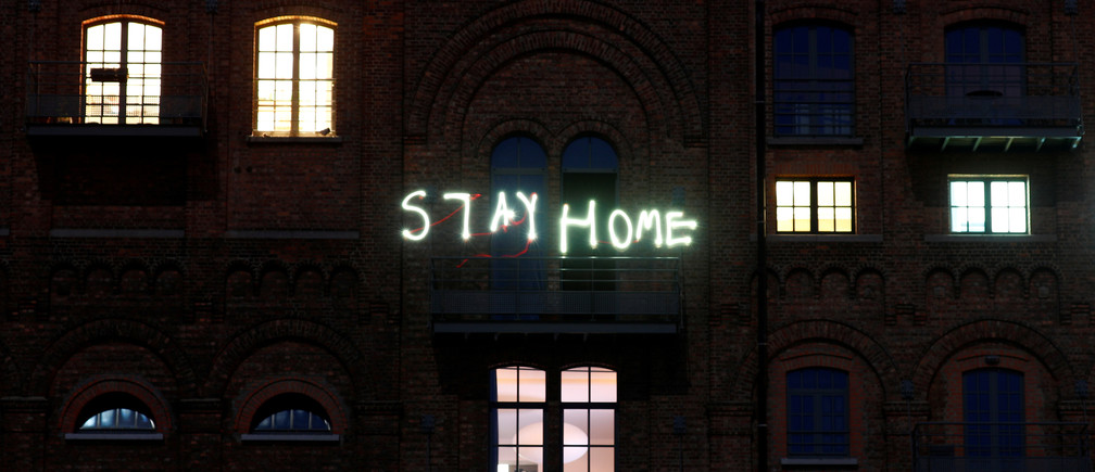 "Residents write words ""stay home"" with their mobile phones as they stand on the balcony of their apartment block during the lockdown imposed by the Belgian government to slow down the coronavirus disease (COVID-19) spread, in Ruisbroek near Brussels, Belgium April 5, 2020. Picture taken with a long exposure. REUTERS/Francois Lenoir - RC2KYF9OLGND"