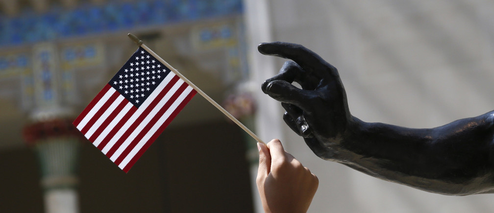 A girl holds a U.S. flag next to a sculpture after a naturalization ceremony at The Metropolitan Museum of Art in New York July 22, 2014. Seventy-five people from 42 countries became American citizens at an event held by U.S. Citizenship and Immigration Services (USCIS) at the Museum. REUTERS/Shannon Stapleton (UNITED STATES  - Tags: SOCIETY POLITICS IMMIGRATION) - RTR3ZPRA