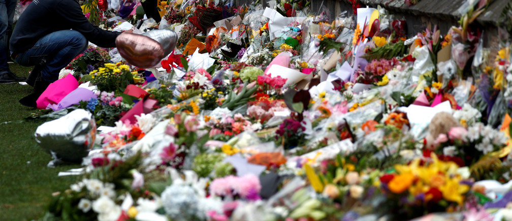 A man places flowers at a memorial site for victims of the mosque shootings at the Botanic Gardens in Christchurch, New Zealand, March 18, 2019. REUTERS/Edgar Su - RC11EE336970