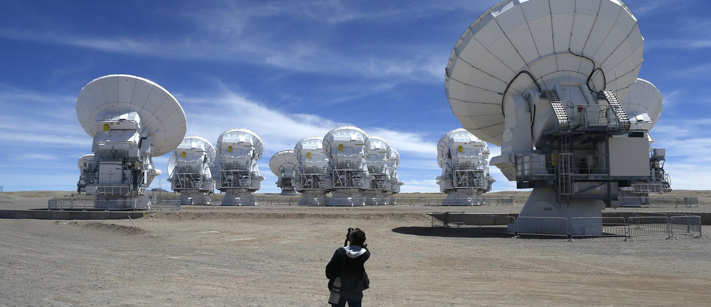 A member of the media takes pictures of the parabolic antennas of the ALMA (Atacama Large Millimetre/Submillimetre Array) project at the El Llano de Chajnantor in the Atacama desert, some 1730 km (1074 miles) north of Santiago and 5000 metres above sea level, March 12, 2013.