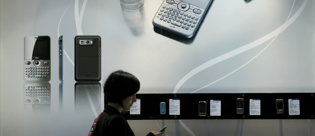 A woman looks at a ZTE N61 mobile phone at a showroom in Shenzhen, China's southern Guangdong province April 16, 2010.