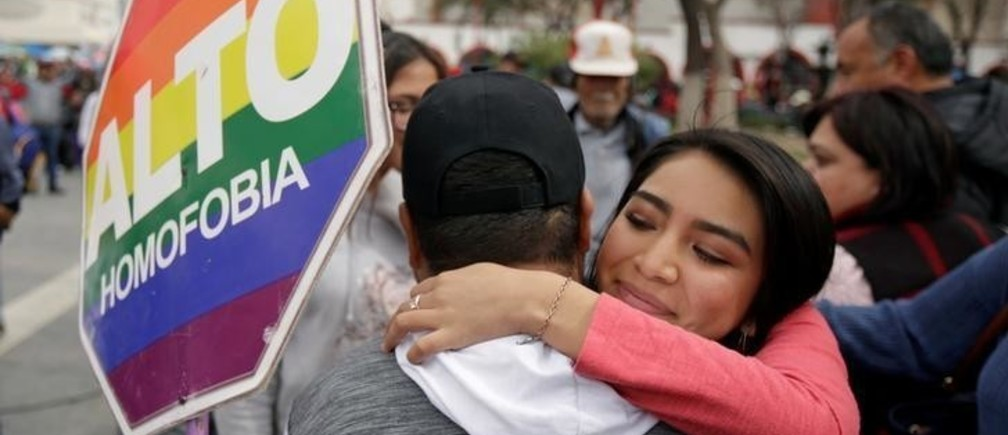 "Members of the LGBT community hold a Hugathon to protest against homophobia and discrimination, in Ciudad Juarez, Mexico February 17, 2018. The poster reads: ""Stop to homophobia"". REUTERS/Jose Luis Gonzalez"