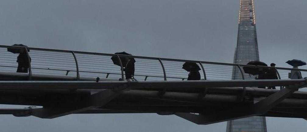 """City workers cross the Millennium footbridge at dawn in front of the Shard skyscraper, in the financial district of London, Britain January 7, 2016. Britain's finance minister George Osborne said on Thursday that Britain's economy was not immune from a """"dangerous cocktail"""" of threats from abroad, and urged against complacency after two years of solid growth. Osborne -- whom Prime Minister David Cameron has named as a possible successor -- said in a new year's message that Britain faced headwinds from slower growth in China, Brazil and Russia as well as tensions in the Middle East.  REUTERS/Toby Melville"""