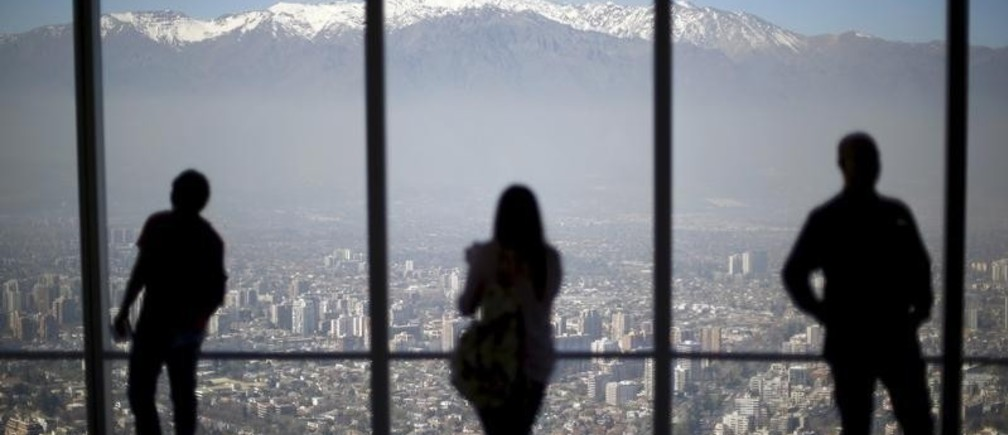 People look out to the Los Andes mountain range next to the city from a rooftop of a commercial center in a business district in Santiago, Chile, September 3, 2015.
