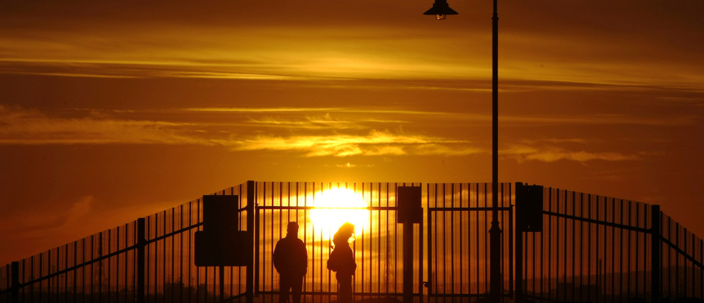 A couple watch a sunset on St Kilda beach in Melbourne July 8, 2009. The development of an El Nino weather pattern is increasing and at this stage may be a medium-strength event, but it could take months for it to be officially declared, Australia's weather bureau said. REUTERS/Mick Tsikas (AUSTRALIA ENVIRONMENT SOCIETY) - GM1E5781BN701