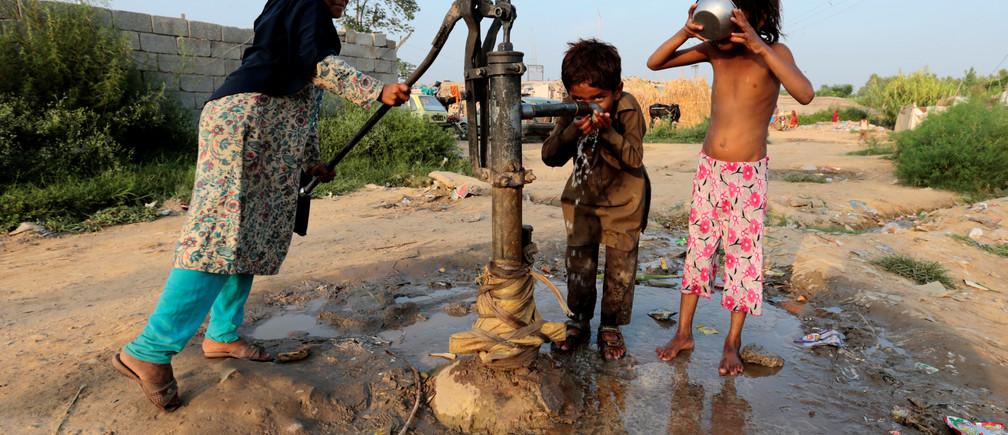 Children drink water from a hand pump in a slum in Islamabad, Pakistan July 19, 2017.  REUTERS/Caren Firouz - RC1EDD666F70