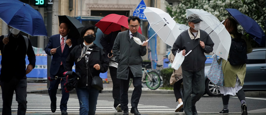 A man holding his mask walks on a zebra crossing among others, amid the spread of the coronavirus disease (COVID-19) in central Seoul, South Korea, April 20, 2020.   REUTERS/Kim Hong-Ji - RC268G9J0A8M