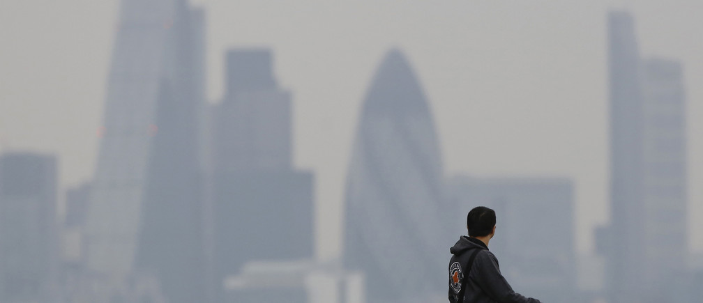 A man walks through Greenwich Park as a haze of pollution sits over the London skyline April 3, 2014. REUTERS/Luke MacGregor - LR1EC5D0UJ08U