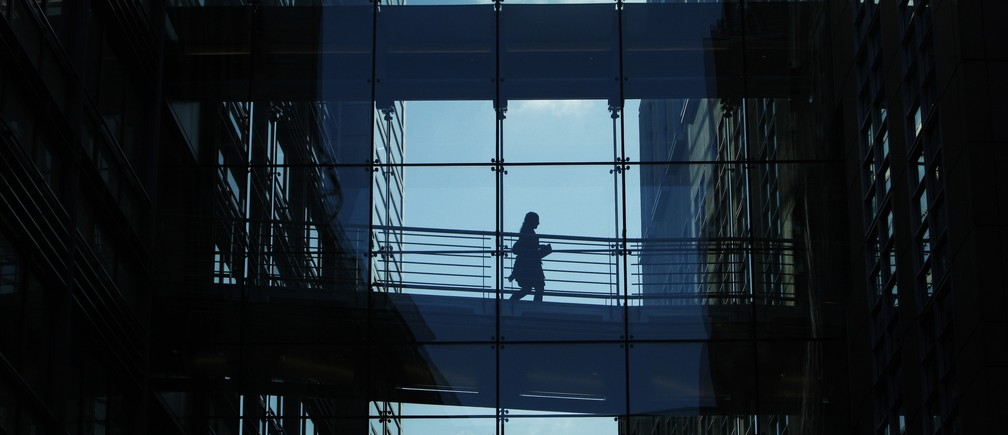 A woman crosses a walkway between Goldman Sachs offices in central London October 15, 2009.