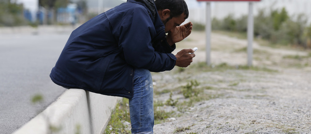 A migrant looks at his mobile phone as he sits near a road sign on the main access route to the Ferry harbour Terminal in Calais, northern France, July 30, 2015.