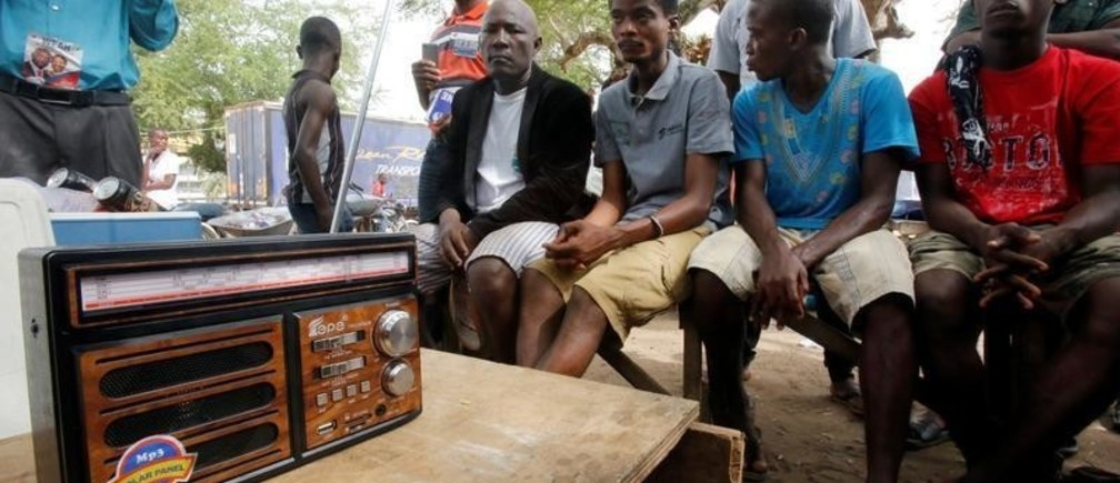 Supporters of George Weah, former soccer player and presidential candidate of Coalition for Democratic Change (CDC), listen to the announcement of the presidential election results on the radio, in Monrovia, Liberia December 27, 2017. REUTERS/Thierry Gouegnon - RC15DD635580