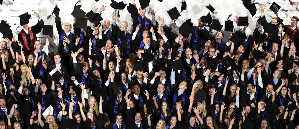 Students throw their mortarboards after their graduation ceremony at the Hamburg School of Business Administration (HSBA) in Hamburg, October 1, 2014.  REUTERS/Fabian Bimmer (GERMANY - Tags: BUSINESS EDUCATION SOCIETY) - RTR48JNX