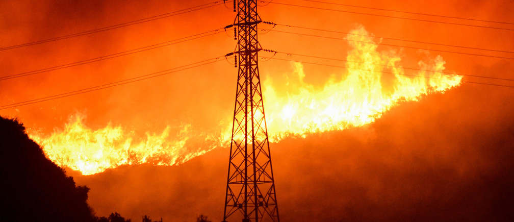 A wind-driven wildfire burns near power line tower in Sylmar, California, U.S., October 10, 2019.  REUTERS/ Gene Blevins - RC1FEA5EE960