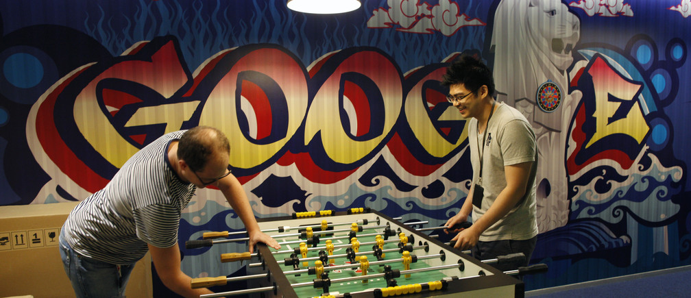 Google's communications manager Robin Moroney (L) plays table soccer with a Google employee at a recreational area of their Singapore office July 8, 2013. Singapore's move to tighten regulation of news web sites, already under fire from bloggers and human rights groups, has attracted criticism from an unexpected quarter - large internet firms with a big presence in the city-state who say the new rules will hurt the industry