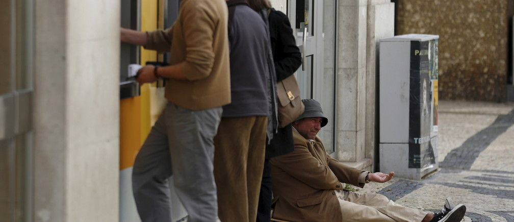 A man begs for money near ATM machines at a Montepio branch in downtown Lisbon, Portugal, April 21, 2016.