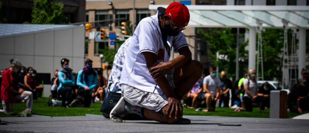 Chris Shelton kneels during a demonstration in downtown Indianapolis, United States. Veronica Holford