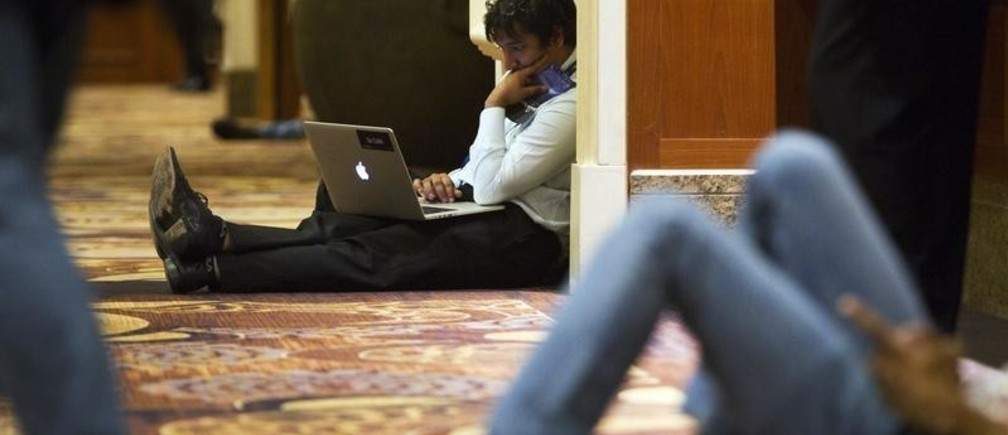 Utkarsh Sanghi, a security engineer at Google, works in a hallway during the Black Hat USA 2014 hacker conference at the Mandalay Bay Convention Center in Las Vegas, Nevada August 6, 2014. REUTERS/Steve Marcus (UNITED STATES - Tags: SCIENCE TECHNOLOGY POLITICS BUSINESS) - GM1EA870JJ201