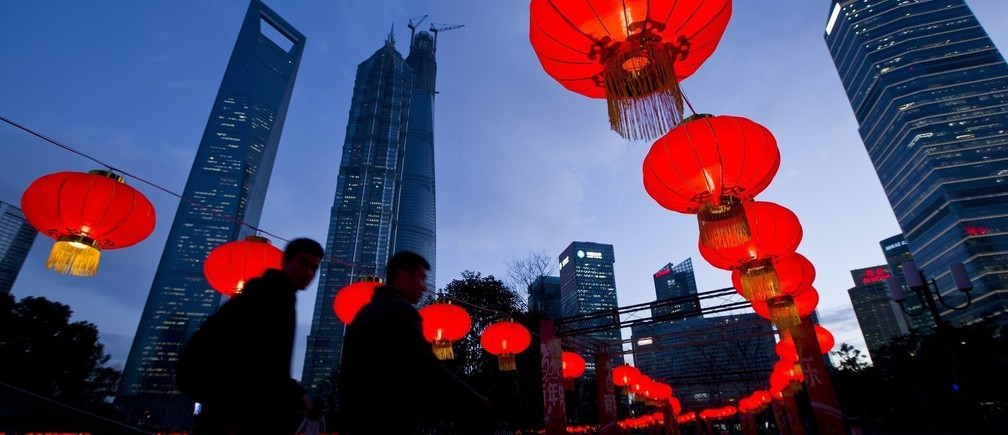 Pedestrians walk under red lanterns which was recently installed as Chinese New Year decorations, at Pudong Financial Area in Shanghai, January 24, 2014. According to the Chinese lunar calendar, the Chinese New Year, which welcomes the year of the horse, kicks off on January 31. Picture taken January 24, 2014. REUTERS/Aly Song