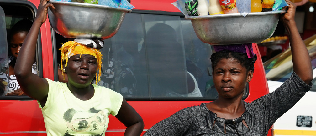 Women carrying drinks on their heads watch as the motorcade that carries the media covering U.S. first lady Melania Trump passes in Accra, Ghana, October 2, 2018. REUTERS/Carlo Allegri - RC16F58BE910