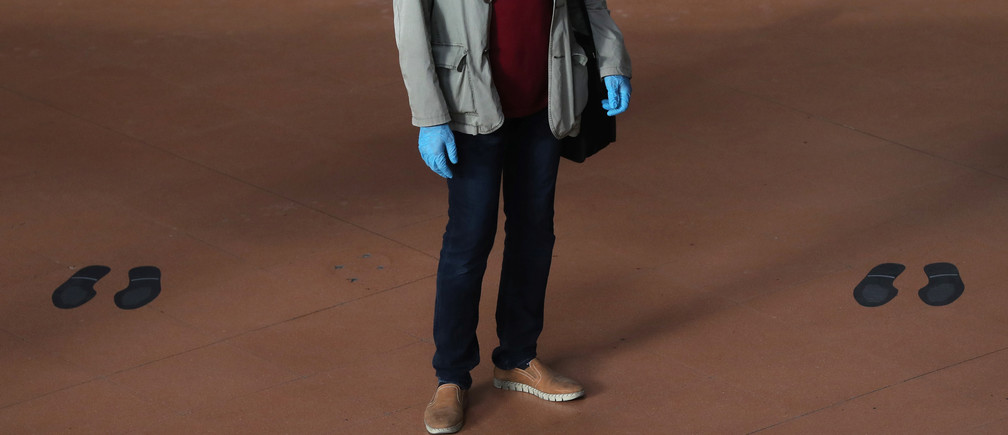 A commuter wearing protective gloves stands amid marks for social distancing on the floor of the Atocha train station, on the first day mask usage is mandatory in public transport, amid the coronavirus disease (COVID-19) outbreak in Madrid, Spain, May 4, 2020. REUTERS/Susana Vera - RC2JHG9IC9AR
