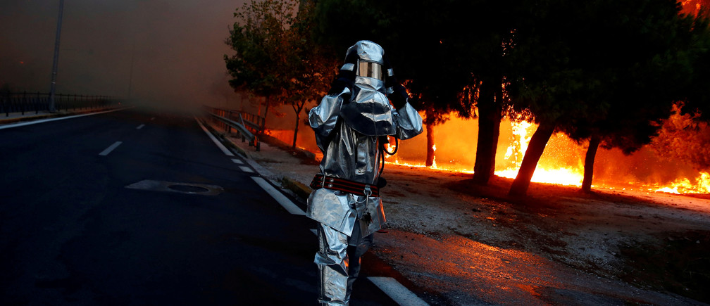 "A firefighter wears a flame resistant uniform as wildfire burns in the town of Rafina, near Athens, Greece, July 23, 2018. REUTERS/Costas Baltas   SEARCH ""POY GLOBAL"" FOR FOR THIS STORY. SEARCH ""REUTERS POY"" FOR ALL BEST OF 2018 PACKAGES. TPX IMAGES OF THE DAY. - RC132F0E53B0"